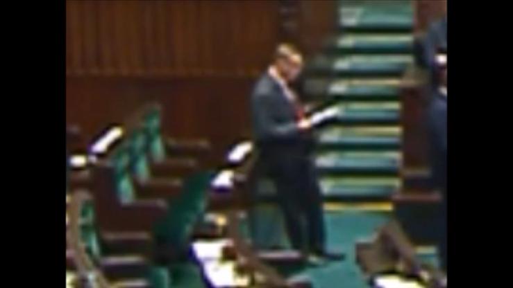 Poseł PO przegląda notatki leżące na miejscu zajmowanym przez prezesa PiS w sali plenarnej